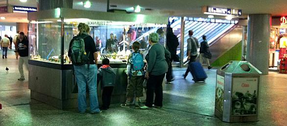 Menschen vor einem Glaskasten mit einer Modelleisenbahn