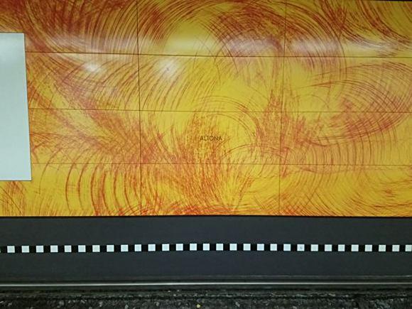 die neue Wandgestaltung im Altonaer Bahnhof zeigt orangene Platten mit Wischmuster und einem kaum leserlichen Altona drauf